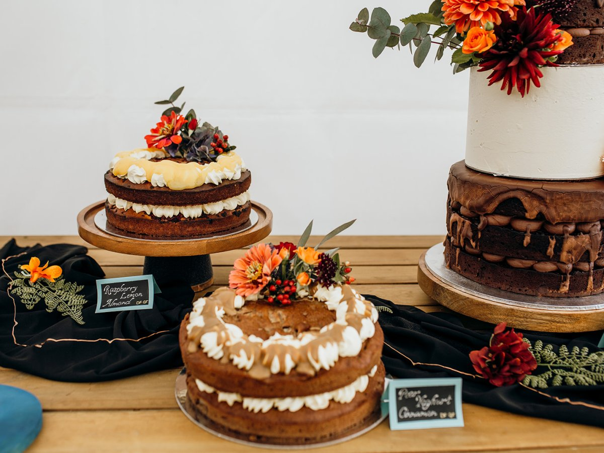A selection of a wedding cake table with three various cake flavours, all decorated beautifully with florals.