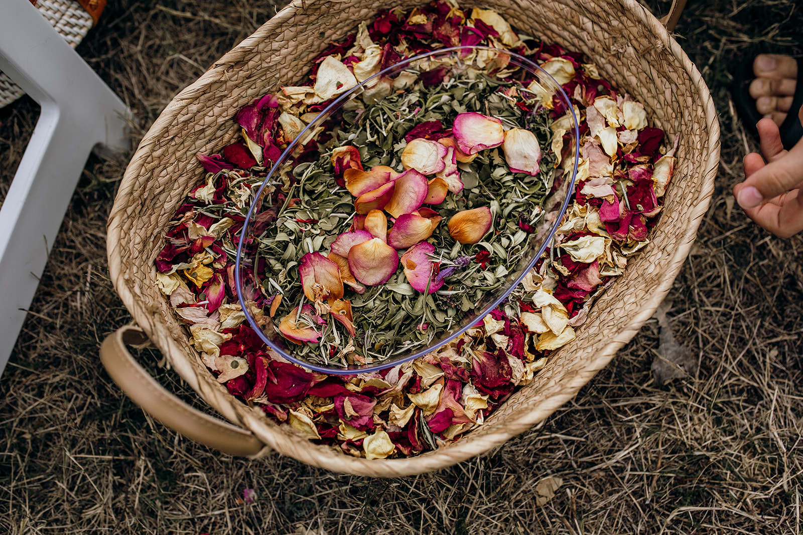 A cane basket sits on the ground full of sustainably dried rose petals and hole punched leaves ready to be thrown as wedding confetti.